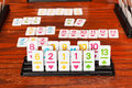Set of tiles in rummy game rack during playing on wooden table Royalty Free Stock Photos