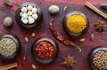 Set of various indian spices on rusted wooden background cumin chili yellow nut spicy mix coriander white black and green cardamon Stock Photo