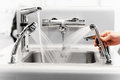 Set of water mixing faucets with hand Stock Photography