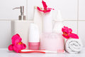 Set of white cosmetic bottles towel and toothbrush with red flo flowers over tiled wall in bathroom Royalty Free Stock Photo
