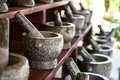 Sets of mortar and pestle in grey and black color granite stone arranging on wooden shelf for sale in local market Royalty Free Stock Photo