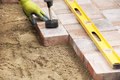 Setting paver installing bricks on patio mallet to level the stones Royalty Free Stock Photos