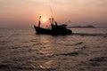 Setting sun behind a fishing boat. Royalty Free Stock Photo