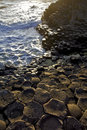 Setting sun highlighting the hexagonal basalt slabs of giants causeway antrim coastline northern ireland is Stock Image