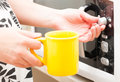 Setting a timer on the microwave oven moving knob with mug in other hand Stock Image