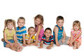 Seven children on the floor are lying and sitting a white background Royalty Free Stock Images