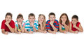 Seven children on floor smiling are lying the a white background Royalty Free Stock Image