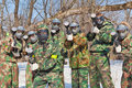Seven friends masks camouflage play paintball fresh air outdoor Stock Photos