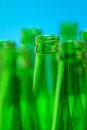 Seven green bottle necks on blue background in center one in focus Stock Photos