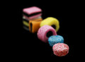 Seven liquorice allsorts candy isolated on black background one in focus and the rest out of focus Stock Images