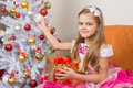 Seven-year girl in beautiful dress sits with a gift and holding a Christmas ball in hands Royalty Free Stock Photo