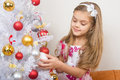 Seven-year girl in beautiful dress treats Christmas toys Royalty Free Stock Photo