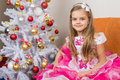 Seven-year girl sitting on a sofa in beautiful dress the Christmas tree Royalty Free Stock Photo