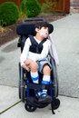 Seven year old biracial disabled boy in wheelchair child has cerebral palsy Royalty Free Stock Photos