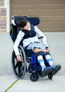Seven year old biracial disabled boy in wheelchair child has cerebral palsy Stock Photo