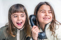 Seven year old girl talking on the old vintage phone and her sis is sister eavesdropping conversation white background Stock Photography