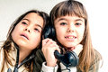 Seven year old girl talking on the old vintage phone and her sis is sister eavesdropping conversation white background Royalty Free Stock Images