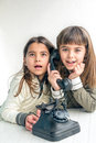 Seven year old girl talking on the old vintage phone and her sis sister is eavesdropping conversation white background Stock Photos
