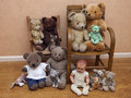 Several children s toys on old chair collection of stuffed animals and antique doll Stock Photos