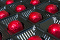 Several chocolates in red foil Royalty Free Stock Photo
