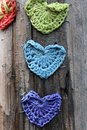 Several colorfully knitted hearts stapled to telephone pole Royalty Free Stock Photo
