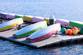 Several colourful small sailing boats demounted and overturned drying on a floating platform