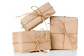 Several gift boxes postal parcels wrapped in brown kraft paper tied with a rope on a white background isolated Stock Photos