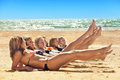 Several girls in bikini lying on sandy beach Royalty Free Stock Photos