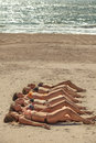 Several girls in bikini lying on sandy beach photo of and tanning the bright summer sun Royalty Free Stock Photos