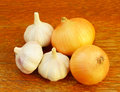 Several heads of garlic and onions on a table Stock Images