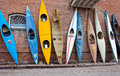 Several old time rustic weathered kayaks stacked against brick wall Stock Photos