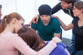 Several people comforting young man on background women another women foreground Royalty Free Stock Photos