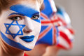 Several people with face art israel and great britain flaga sre painted on faces Stock Photo