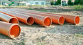 Several plastic pipes used in construction orange for drainage or the sewerage on a building site Royalty Free Stock Image
