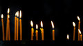Several tall candles lit in a church dark room Royalty Free Stock Image