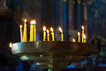 Several tall candles lit in church a dark room Royalty Free Stock Photography