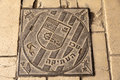 Sewage lid with the emblem of the ancient city of acco acre in israel inscribed on it the text in hebrew and arabic trnaslates to Stock Image