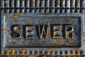 Sewer access cover with rusty iron a printing Royalty Free Stock Images