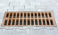 Sewer grate rusty cast iron storm grating on the sidewalk stacked gray tiles Royalty Free Stock Image