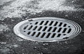 Sewer manhole on the urban asphalt road closeup photo Royalty Free Stock Image