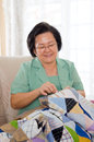 Sewing asian senior woman a blanket Stock Image