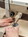 Sewing closeup of senior woman s hands sawing linen border with machine Royalty Free Stock Photo