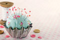 Sewing concept background with floral pincushion green handmade in an old metal cupcake buttons and spools of thread and lace Royalty Free Stock Photo