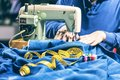 Sewing denim jeans with sewing machine. Repair jeans by sewing machine. Alteration jeans, hemming a pair of jeans, handmade Royalty Free Stock Photo