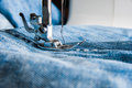 Sewing machine and blue jeans fabric. Royalty Free Stock Photo