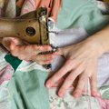 stock image of  On the sewing machine embroiders the girl