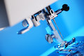Sewing machine foot modern on blue background with copy space Stock Images