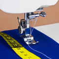 Sewing machine, thread and a yellow measuring tape Royalty Free Stock Photos