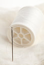 Sewing needle and thread macro of on white fabric Stock Images