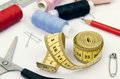 Sewing spools, scissors and tape measure on white cloth Royalty Free Stock Photo